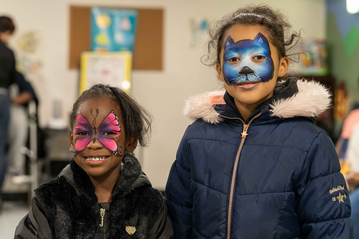 Two young girls with face paint new neighborhoods