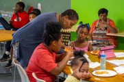 woman helping young girls with food at new neighborhoods summer kick off