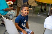 young boy smiling at new neighborhoods summer kick off