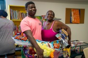 young man and woman smile with gifts at new neighborhoods summer kick off