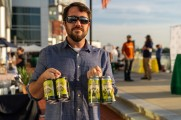 Omme Gang Nirvana IPA Representative holding up 4 packs of beer