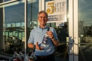 5th State Distillery manager holding up a bottle of Asylum Gin