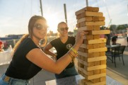 Two women playing Jenga as one smiles at the camera