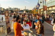 A large group of people interacting with beer and whiskey vendors