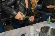 A woman pouring Suntory Japanese whiskey into a shot cup