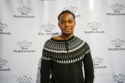 A man in front of a New Neighborhoods step and repeat