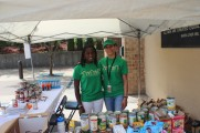 Two Female Staff Members Smiling at Collection Table For A Food Bank at the 2016 Health Fair