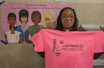 woman holding the witness project pink shirt at healthy harvest 2017