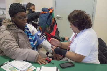 woman taking another womans blood pressure at 2017 healthy harvest
