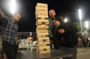 Two Men and A Woman Having Fun Playing Jenga at the 2016 Jazz On The Rocks