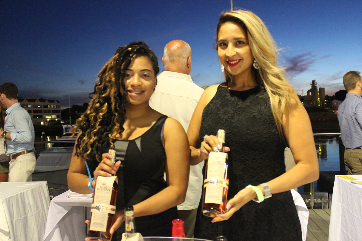Two Woman Smiling With Whiskey Bottles at the 2016 Jazz on the Rocks