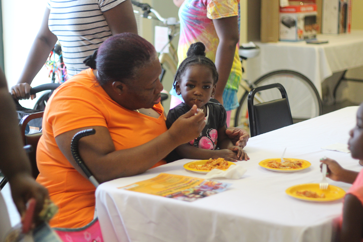 Woman Feeding Little Girl Food at Summer Meals Celebration 2016