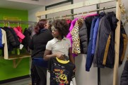 Young Girl and Woman Look Through Coats on Coat Rack At 2016 Winter Warmup