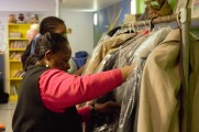 Women Looking Through Coats On Coat Rack At the 2016 Winter Warmup