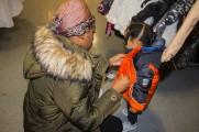woman helps little girl zip jacket at 2017 winter warm up new neighborhoods