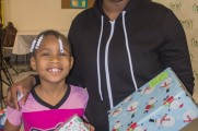 Woman and Young Girl Smile And Hold Presents At Winter Warmup 2017