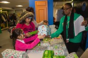 Young Girls Receive Gifts From Staff Member At Winter WarmUp 2017