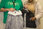 Staff Member and Women Hold Coats at Winter Warmup 2017