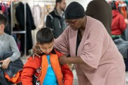 woman helps young boy zipper coat at 2018 winter warmup new neighborhoods