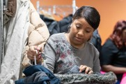 woman looking through coats at 2018 winter warm up new neighborhoods