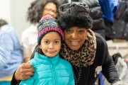 woman smiles with young girl at 2018 winter warm up new neighborhoods