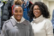 Two women smile in front of coat rack at 2018 winter warm up new neighborhoods