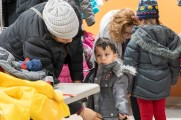 women help young children zipper coats at 2018 winter warm up new neighborhoods