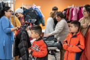 women help young boys at winter warm up 2018 new neighborhoods