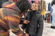 woman helps zip up young boys coat at winter warmup 2018 new neighborhoods