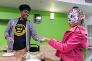 man serves food to young girl with face paint at winter warm up 2018 new neighborhoods