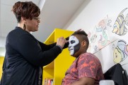 woman gives young boy face paint at 2018 winter warmup new neighborhoods