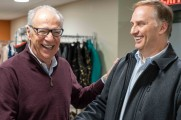 two men laugh in front of coat racks at 2018 winter warmup new neighborhoods