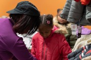 woman helps zip young girls coat at winter warm up 2018 new neighborhoods