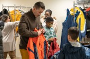 man helps young boy with coat at winter warm up 2019 new neighborhoods