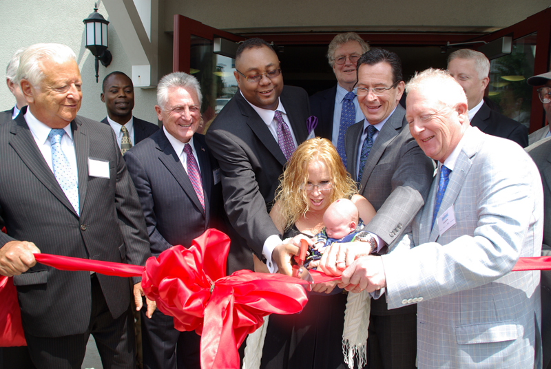 Men and women cutting a red ribbon for Elmcrest Terrace