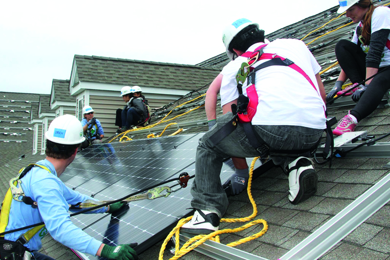 Men and women installing solar panels on a rooftop