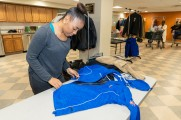 New Neighborhoods employee preparing a coat for winter warm up