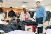 New Neighborhoods employees gathering around a table of coats