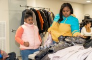 A woman and her daughter looking at free coats at the winter warmup event in stamford