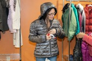 A woman trying on a grey bubble jacket