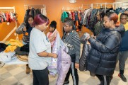 A group of women trying on coats at the 2019 Winter Warmup