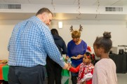 Jamey Healy handing out candy canes to children at the 2019 Winter Warmup