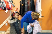 A woman checking the coat fitting for a young girl