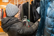 A woman looking through a rack of free coats at the Winter Warmup coat drive