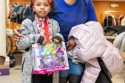 A young girl and her grandmother dressed for Christmas show off their gifts